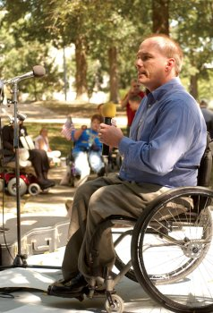 man in wheelchair speaking up at community event.