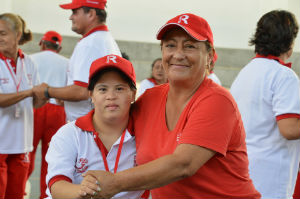 grandmother or parent hugging daughter that has downs syndrome while at her sports event