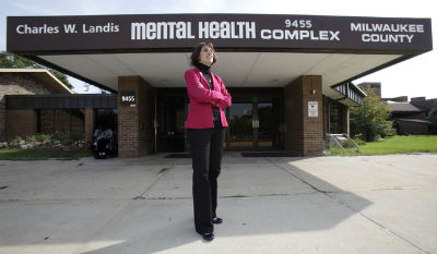 Barbara Beckert standing in front of Milwaukee county Mental Health Complex with arms crossed.