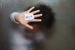 hand on window showing a sign for help