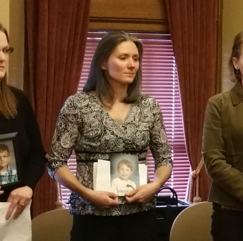 Quinton's mother, holding a picture of her son at a hearing for Seclusion and Restraint legislation