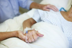 patient holding hands with family member