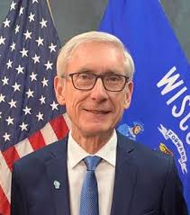 Tony Evers headshot with US and Wisconsin flags in background