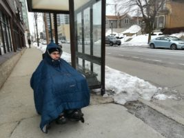 William Crowley awaits bus wearing parka in winter