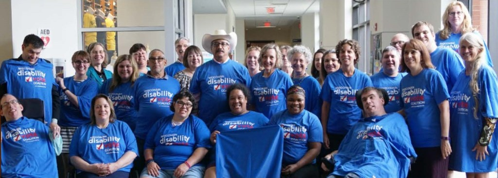 Group of about 30 people posing together in Wisconsin Disability Vote Coalition t-shirts and smiling