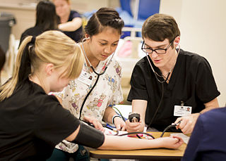 Three CNA students gathered around a table, studying