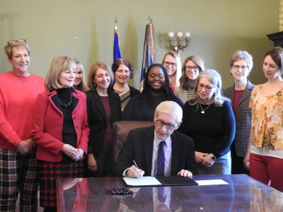 Governor Evers signing bill at table with group standing around him