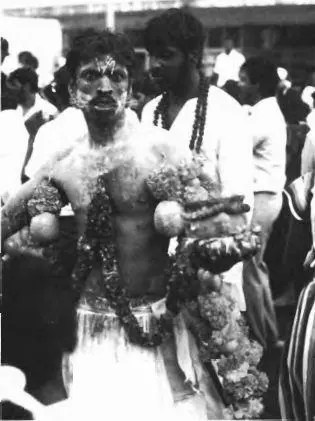 Devotee in a trance. His face is adorned with pins and two skewers through his cheeks; his body is smeared with ash and limes and marigold chains dangle from hooks through his flesh. (Photograph: Awhor' s collection)