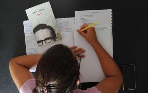 Una ragazza scrive qualche appunto da un libro universitario. Sulla scrivania, anche il libro Stoner, di John Williams