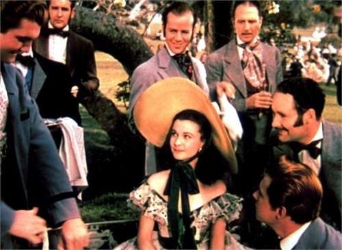 Rossella O'Hara, protagonista del film Via col vento sorride circondata da amici uomini. È la terza tra le donne indipendenti nella letteratura di cui parliamo oggi