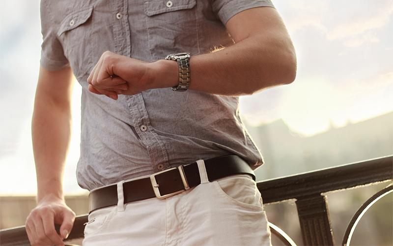 Un uomo guarda il suo orologio per essere sicuro di non perdere tempo
