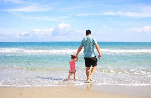 Padre e figlia passeggiano sulla spiaggia
