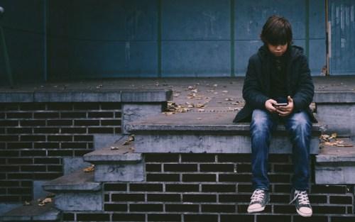 Bambino con un cellulare: starà navigando su internet?
