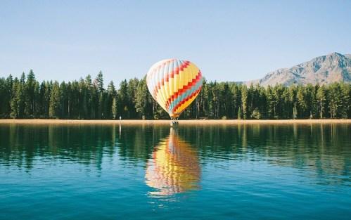 Una mongolfiera riflessa su un lago