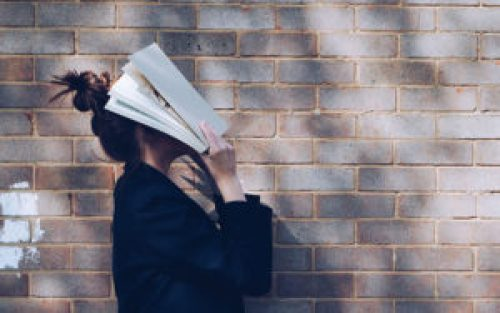 Una donna con un libro sul viso