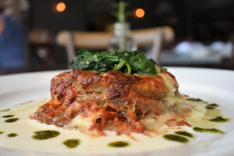 Parmigiana di Melanzane - layers of eggplant, tomato sauce and mozzarella topped with fresh spinach | Photo Credit Bettolino Kitchen