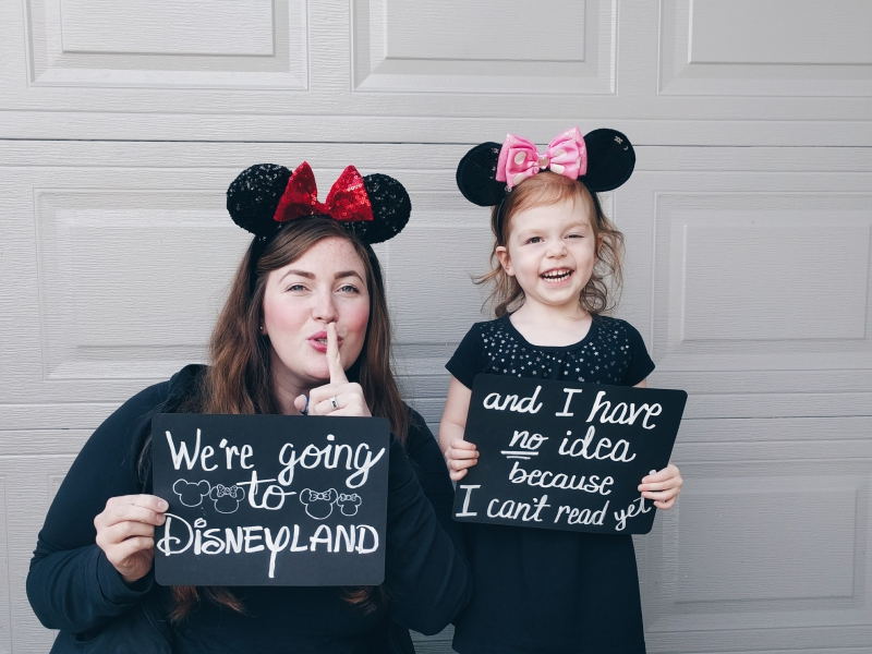 """Mother-daughter trip to Disneyland, mom and daughter holding signs that read """"We're going to Disneyland... and I have no idea because I can't read yet!"""""""