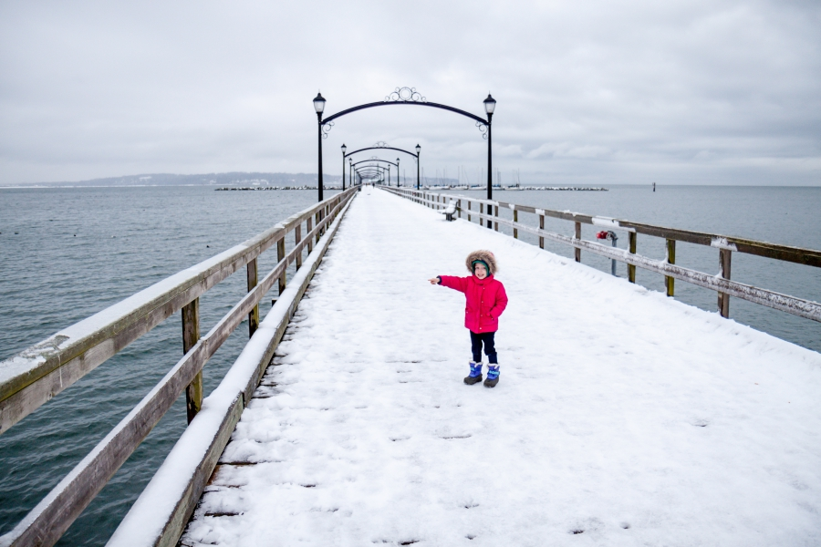 Girl standing on pier at White Rock in BC