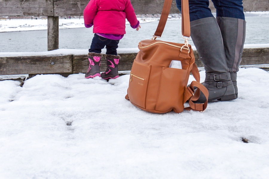 Mother and her daughter on pier of White Rock with Fawn Design diaper bag in brown.
