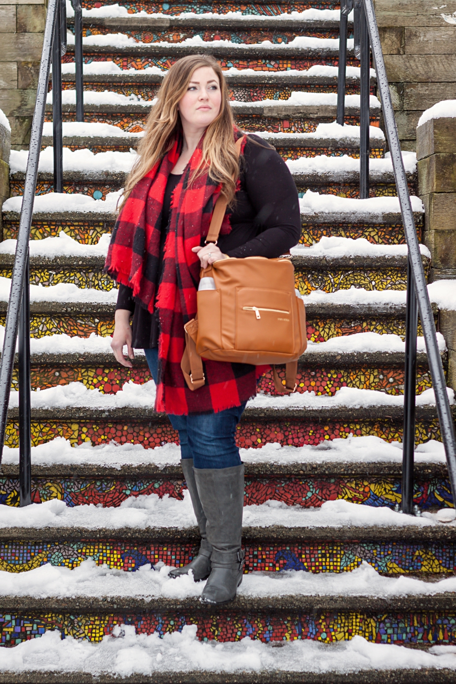Fawn Design diaper bag, brown version. Photo of standing on a colourful staircase.