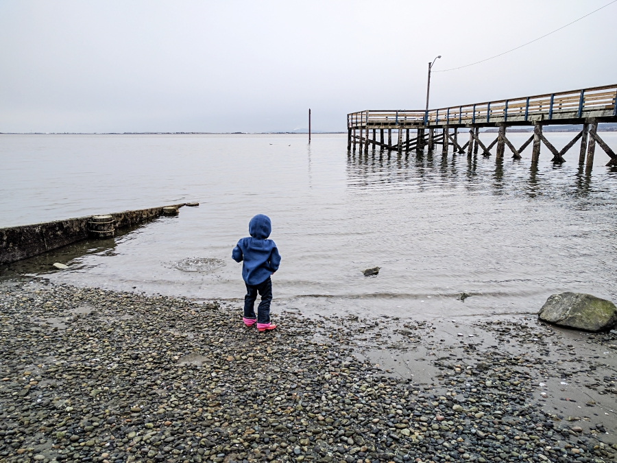 anxiety: pier stretching out to the ocean, child playing at the beach near the ocean's edge