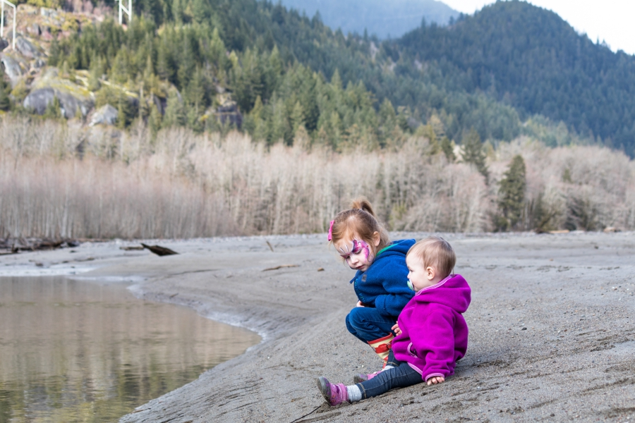 Squamish River Estuary, preschooler and toddler playing on the rivers edge