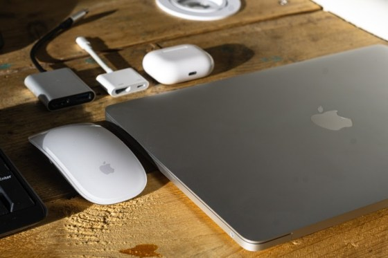 A Macbook on a desk next to a mouse
