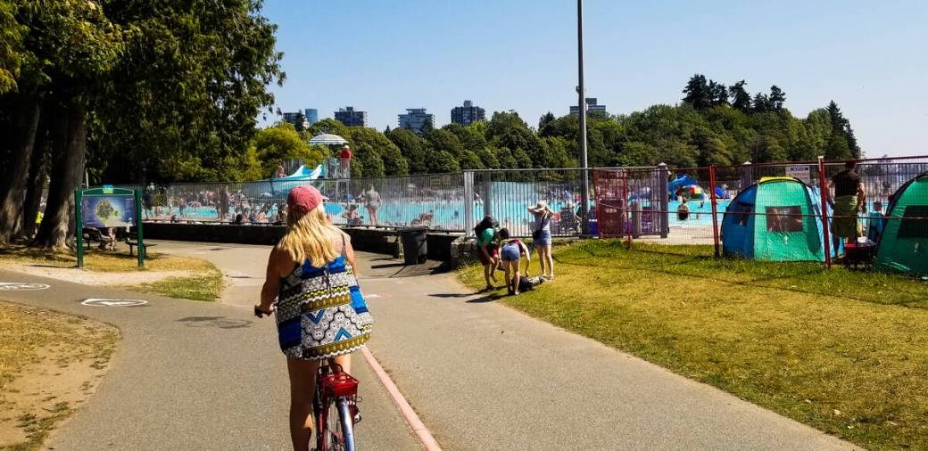 Rear view of a girl cycling along seawall past a swimming pool