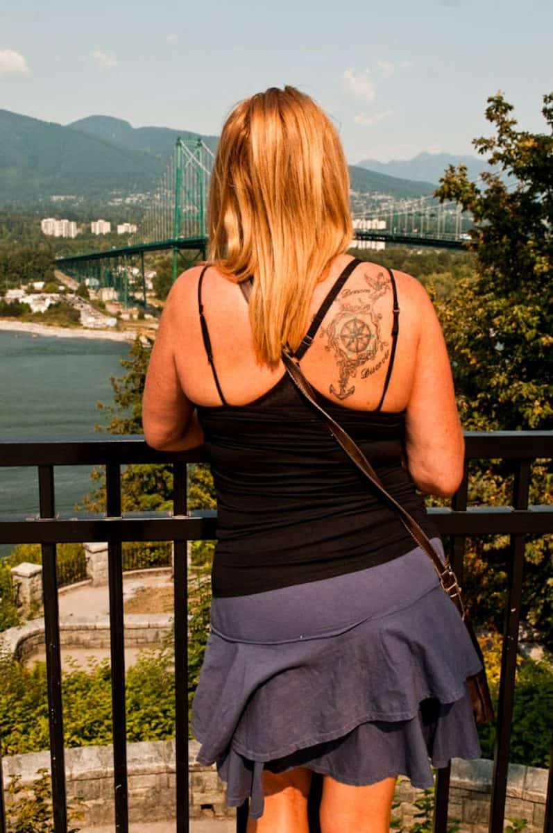 Back view of a girl with blonde hair and a shoulder tattoo looking out over Prospect Point in Stanley Park Vancouver