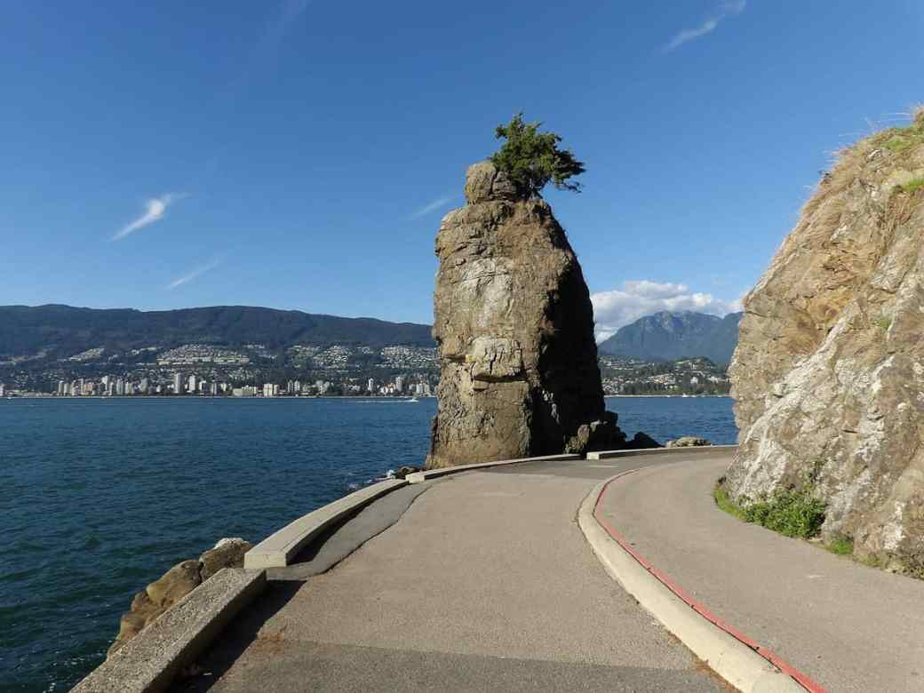 Siwash Rock with a tree on top on the Stanley Park Seawall