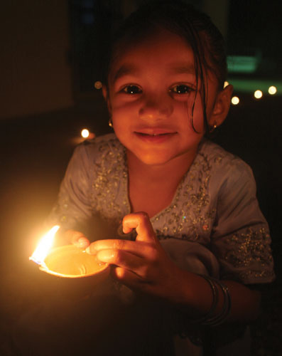 A little girl holds a deya at Divali. Photographer: Shirley Bahadur