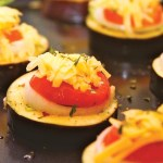 Sliced baigan (melongene) topped with fresh tomato, onion, cheese and local herbs. Photographer: Marc Seyon/Very Caribbean Ltd (verycaribbean.com)