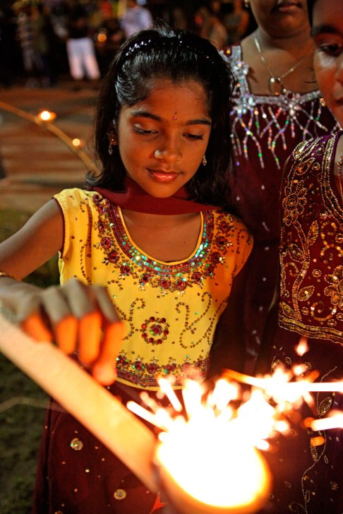 A little girl lights a starlight from a deya at Divali. Photo by Stephen Broadbridge
