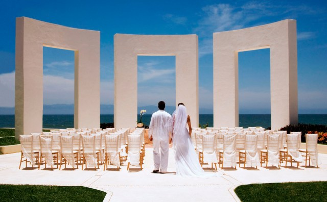 A bride and groom standing in front of a monument in Riviera Maya.