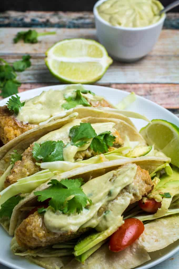 Crispy, juicy oven-fried fish smothered in a creamy, spicy avocado sauce and nestled in a warm tortilla. These Oven Fried Fish Tacos with Spicy Avocado Cream Sauce are simply perfect. Top with crunchy cabbage, cilantro, and a squeeze of fresh lime for an incredible flavor in this insanely easy-to-make dish!