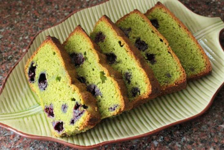 A green loaf cake studded with purple blueberries