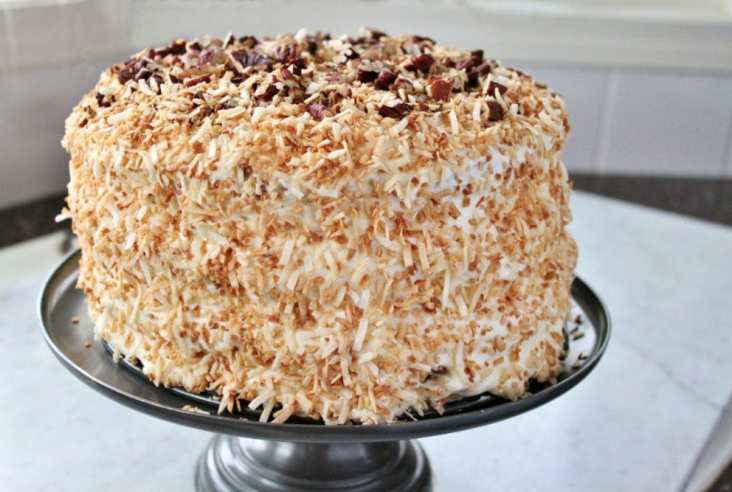 A decadent cream cake with pecans and coconut