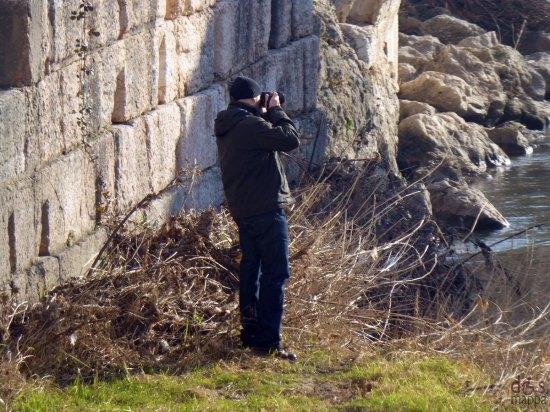 fotografo in riva all'adige sotto ponte pietra a verona