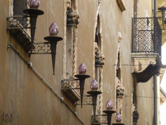 palazzo antico verona con finestre a trifora, fiaccole viola e balcone con ringhiera in ferro con stemma scaligero