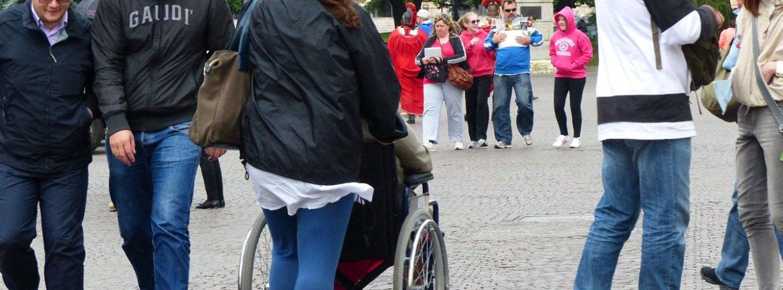 foto in piazza bra a verona con signora anziana in carrozzina con accompagnatrice