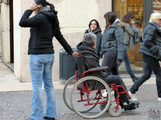 verona, via cappello: signora disabile in carrozzina con accompagnatrice al telefono cellulare