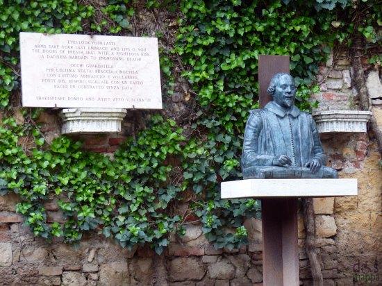 il busto di william shakespeare con targa con citazione di giulietta e romeo all'entrata della tomba di giulietta a verona