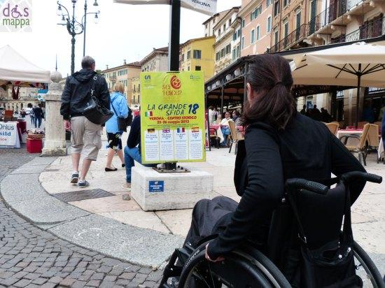 donna disabile in carrozzina davanti al manifesto della grande sfida in piazza bra a verona