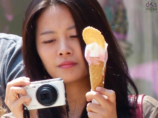 ragazza asiatica scatta una fotografia in piazza delle erbe a verona