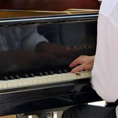 pianista suona il pianoforte in piazza delle erbe a verona, close up su mani e tasti