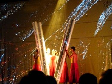 """la funambolica compagnia fondata e diretta da Moses Pendleton (che di Alchemy è autore e coreografo) torna al Teatro Romano con un evento speciale andato in scena in prima mondiale lo scorso febbraio. Lo spettacolo (a Verona in esclusiva estiva per il Nord Italia) svela i segreti dei quattro elementi primordiali – terra, aria, acqua e fuoco – creando arcane suggestioni in grado di trasportare lo spettatore in una dimensione surreale. «Gli antichi alchimisti – sottolinea Pendleton – non lavoravano da soli: evocavano gli spiriti perché li aiutassero nei loro riti segreti. Allo stesso modo gli interpreti di Alchemy si elevano ad """"apprendisti stregoni"""" per esplorare i più reconditi meandri alchemici attraverso la magica spiritualità e la parallela corporeità della danza». In una felice commistione di danza contemporanea e di illusionismo, su musiche di autori vari (tra cui Danna & Clement, Daimon, Escala, Ennio Morricone, Oreobambo, Magna Canta, Liquid Bloom e Silvard) e in un'atmosfera che sottolinea forti istanze ecologiste, due frasi di Moses Pendleton riportate sul programma di sala sintetizzano lo spettacolo: la prima è che """"da qualche parte c'è sempre l'oro se scavi a fondo"""", la seconda è """"se non cogli il ritmo, non cogli il succo"""". Ci prova gusto, Pendleton, ad assemblare fenomenologie scientifiche e letterarie e così, in linea con la multimedialità fiabesca dei suoi spettacoli, tira in ballo lo scienziato Isaac Newton e il poeta-scrittore William Butler Yeats. «Il mutamento dei corpi in luce e della luce nei corpi – sottolinea Pendleton citando Newton – è strettamente conforme al corso della natura che sembra prediligere le trasformazioni». Di Butler Yeats fa invece suo un poetico passo notturno di Rosa alchemica: «Scostai le tende e guardai fuori nel buio, e alla mia fantasia turbata tutti quei puntini di luce che riempivano il cielo parvero i fornelli di innumerevoli alchimisti divini, che lavorassero continuamente a trasformare il piombo in oro, la stanchezza"""