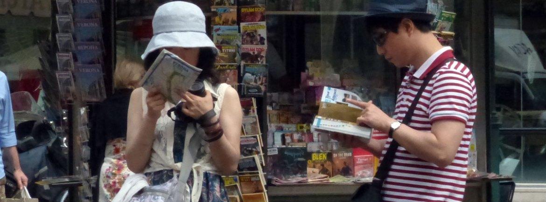 turisti asiatici consultano mappe e guide di verona davanti all'edicola di via cappello a verona