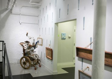 """l'elefante sulla sedia a rotelle """"L'artiste,"""" by the collaborative !ND!V!DUALS, is a scrap-wood sculpture of an elephant in a wheelchair admiring drawings of elephant exploits."""