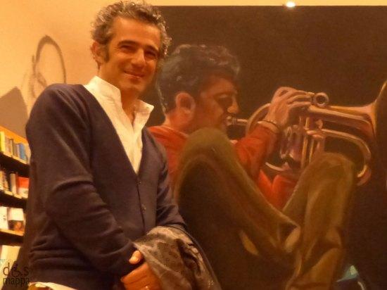Paolo Fresu posa davanti il ritratto di Andrea Sambugaro