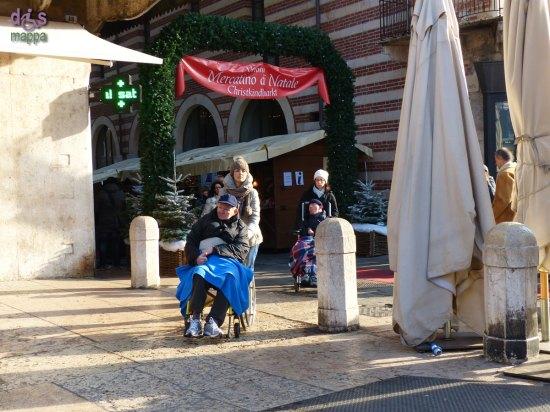 Due signori disabili in carrozzina con accompagnatrici si dirigono alla rampa in Piazza delle Erbe dopo aver visitato il mercatino di Natale